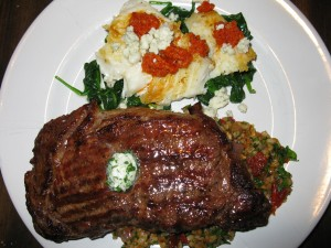 Surf and Turf Entree; On Top:  Pan-Seared Halibut on a Bed of Spinach Topped with Sundried Tomato Coulis and Bleu Cheese; On Bottom:  Grilled Rib-Eye Steak Topped with Herb Butter on a Bed of Brown Rice Pilaf